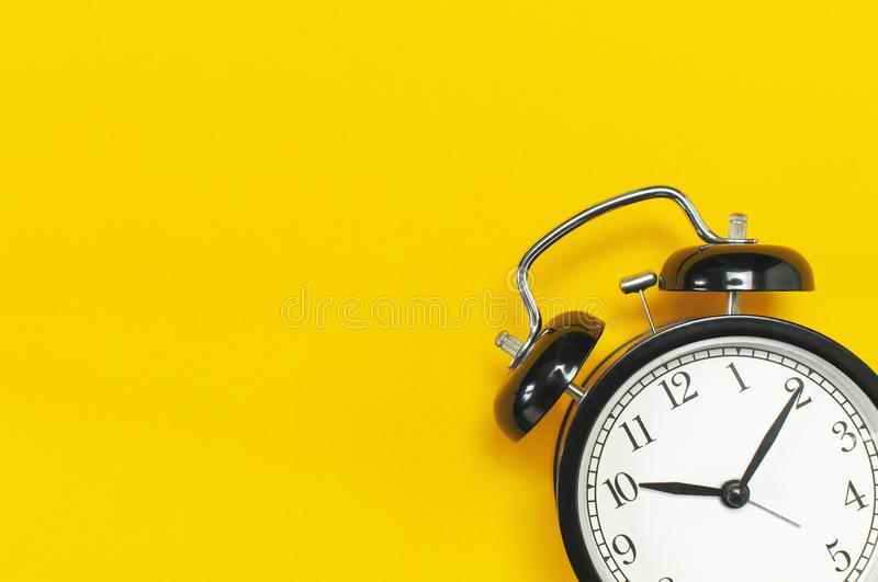Black retro alarm clock on yellow background top view Flat lay copy space. Minimalistic background, concept of time, deadline,. Time to work, morning stock photos