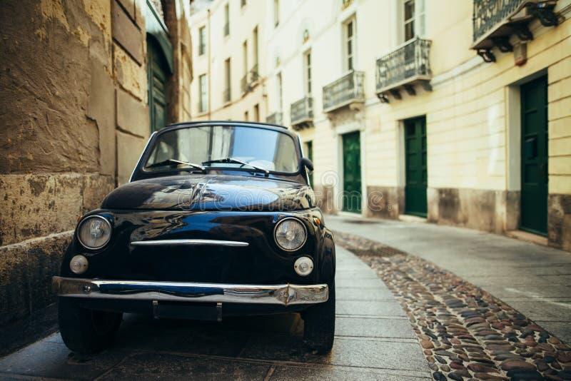 Black retro car parked on narrow italy street in Sardinia island royalty free stock photography