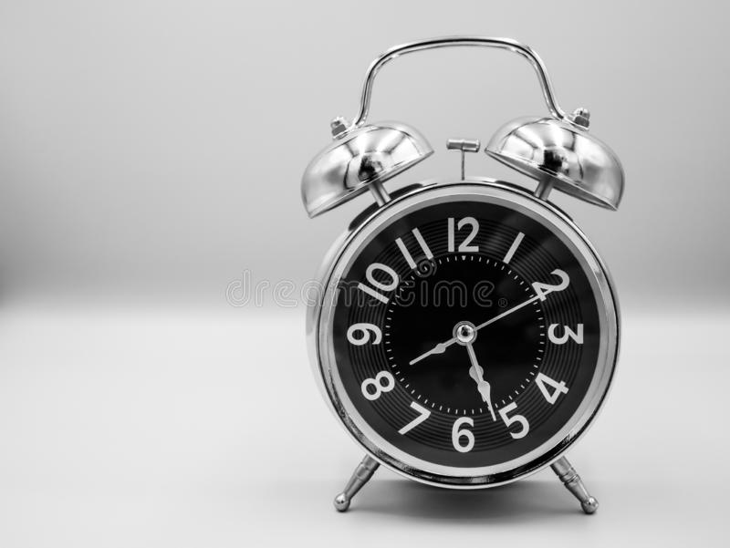 Black retro with silver border alarm clock that represent number of analog on isolated white background royalty free stock photo