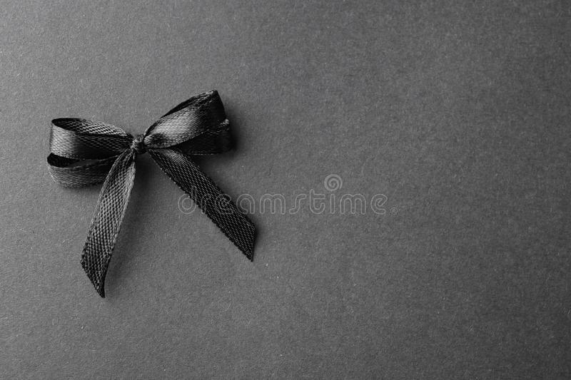Black ribbon bow on dark background, top view with  for text. Funeral symbol. Black ribbon bow on dark background, top view with space for text. Funeral symbol stock photos