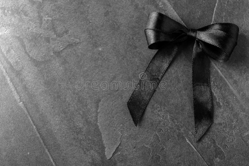 Black ribbon bow on dark grey stone surface, space for text. Funeral symbol. Black ribbon bow on dark grey stone surface, top view with space for text. Funeral royalty free stock photo