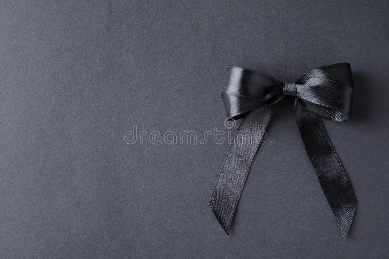 Black ribbon bow on dark , top view with space for text. Funeral symbol. Black ribbon bow on dark background, top view with space for text. Funeral symbol royalty free stock photo