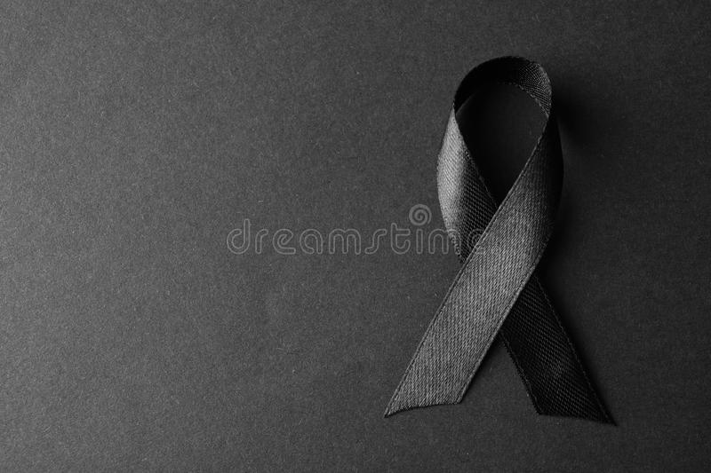 Black ribbon on dark background, space for text. Funeral symbol. Black ribbon on dark background, top view with space for text. Funeral symbol stock images