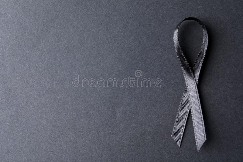 Black ribbon on dark background, space for text. Funeral symbol. Black ribbon on dark background, top view with space for text. Funeral symbol stock photo