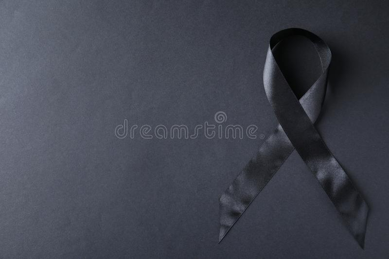 Black ribbon on dark background, top  with space for text. Funeral symbol. Black ribbon on dark background, top view with space for text. Funeral symbol royalty free stock photos
