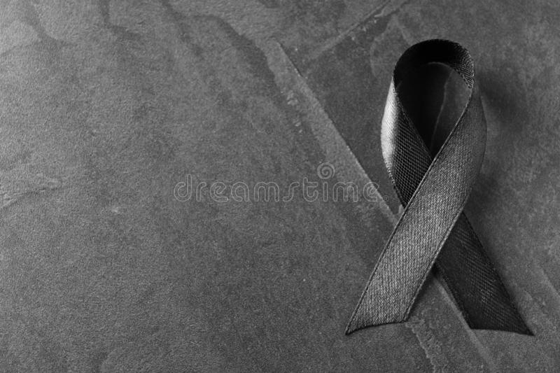 Black ribbon on dark grey stone surface, topwith space for text. Funeral symbol. Black ribbon on dark grey stone surface, top view with space for text. Funeral royalty free stock images