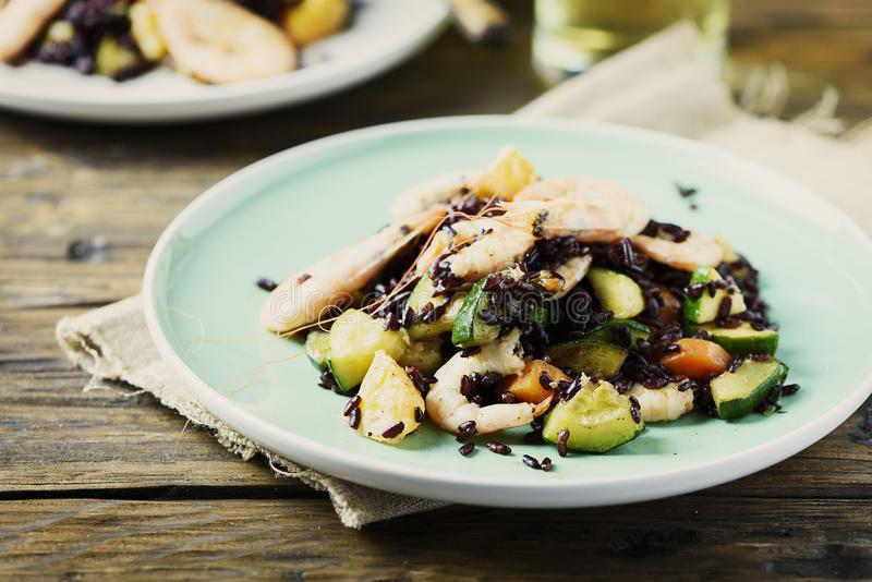 Black rice with prawns, vegetables and orange royalty free stock photo