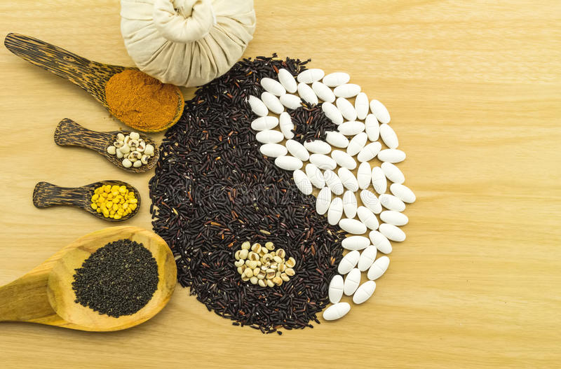 Black rice and white pill forming a yin yang symbol and Spa herbal. Compressing ball , turmeric powder , millet , soybean , basil seed in wooden spoon on brown stock photos