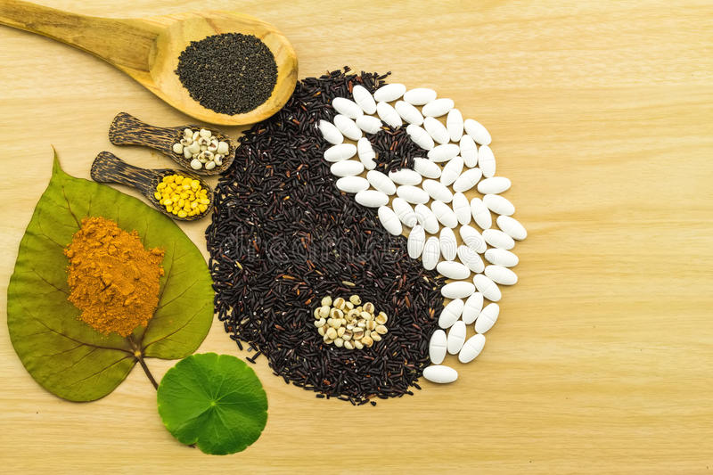 Black rice and white pill forming a yin yang symbol and Spa he. Rbal compressing ball , turmeric powder , millet , soybean , basil seed in wooden spoon on brown royalty free stock images