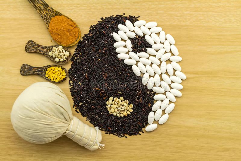 Black rice and white pill forming a yin yang symbol and Spa he. Rbal compressing ball , turmeric powder , millet , soybean , basil seed in wooden spoon on brown royalty free stock photography