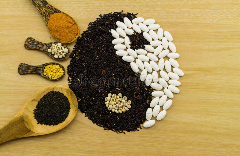 Black rice and white pill forming a yin yang symbol and turme. Ric powder , millet , soybean , basil seed in wooden spoon on brown wooden indicate blending of stock photo