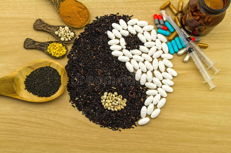 Black rice and white pill forming a yin yang symbol and turmer. Ic powder , millet , soybean , basil seed in wooden spoon ,syringe ,bottle on brown wooden stock images