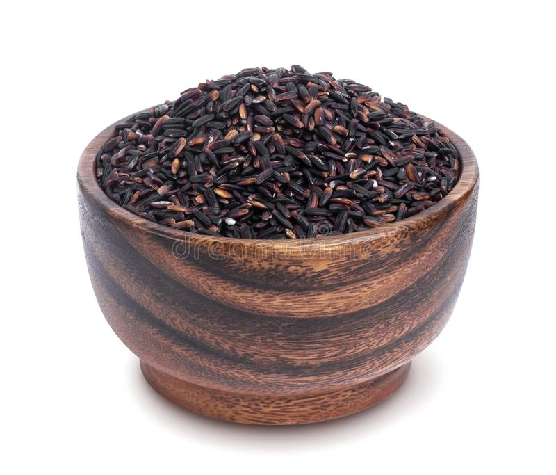 Black rice in wooden bowl isolated on white background royalty free stock photography