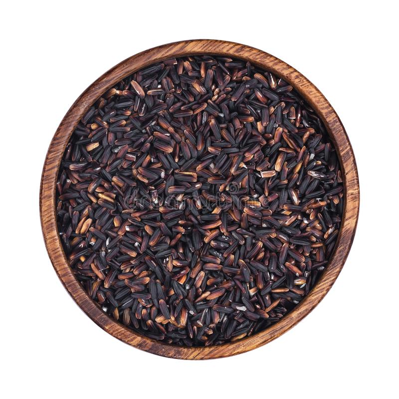 Black rice in wooden bowl isolated on white background. Top view royalty free stock images
