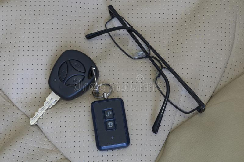 Black-rimmed glasses and car keys lying on the chair in eco-leather stock photos