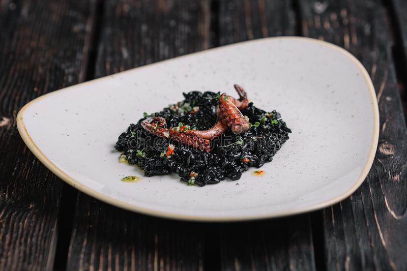 Black risotto with cuttlefish ink and octopus tentacles on irregular shape plate royalty free stock photography