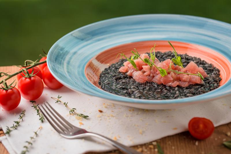 Black risotto with slices of salmon garnished with microgreen. In a plate stock images