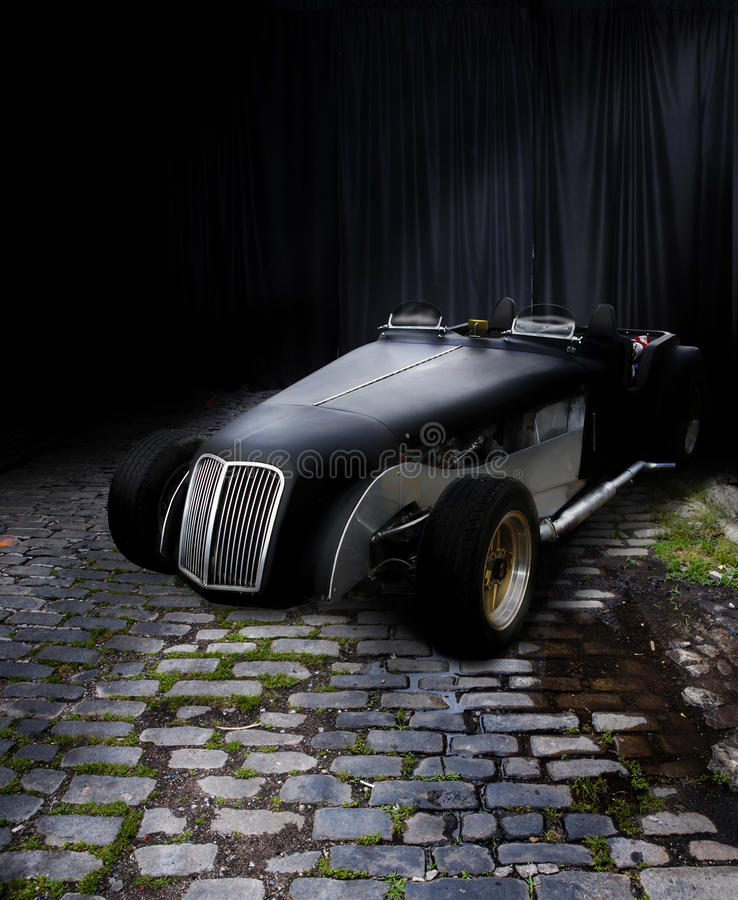 Black roadster. A black roadster car on a wet brick surface with a black curtain in the background. Concept for car show royalty free stock photo