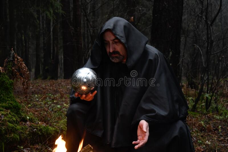 A black-robed monk sits by a fire in the forest and looks into a divination ball. Mysticism and magic, sorcerers and witches 3. A black-robed monk sits by a fire royalty free stock image