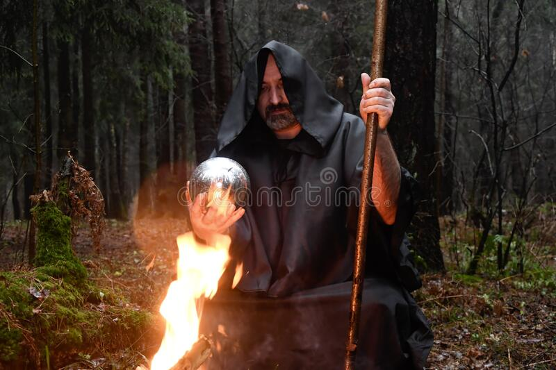 A black-robed monk sits by a fire in the forest and looks into a divination ball. Mysticism and magic, sorcerers and witches 3. A black-robed monk sits by a fire stock photo