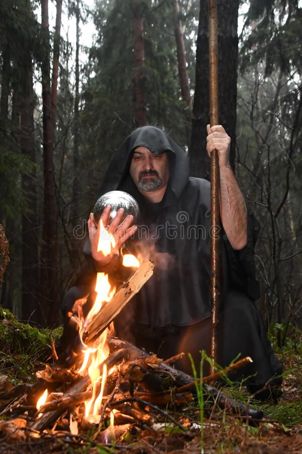 A black-robed monk sits by a fire in the forest and looks into a divination ball. Mysticism and magic, sorcerers and witches 3. A black-robed monk sits by a fire stock photos
