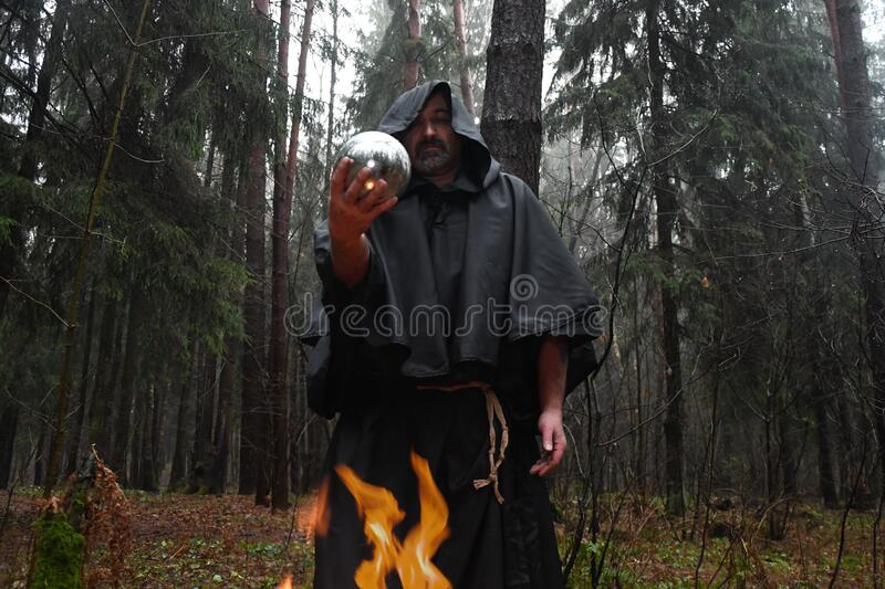 A black-robed monk sits by a fire in the forest and looks into a divination ball. Mysticism and magic, sorcerers and witches 3. A black-robed monk sits by a fire stock image
