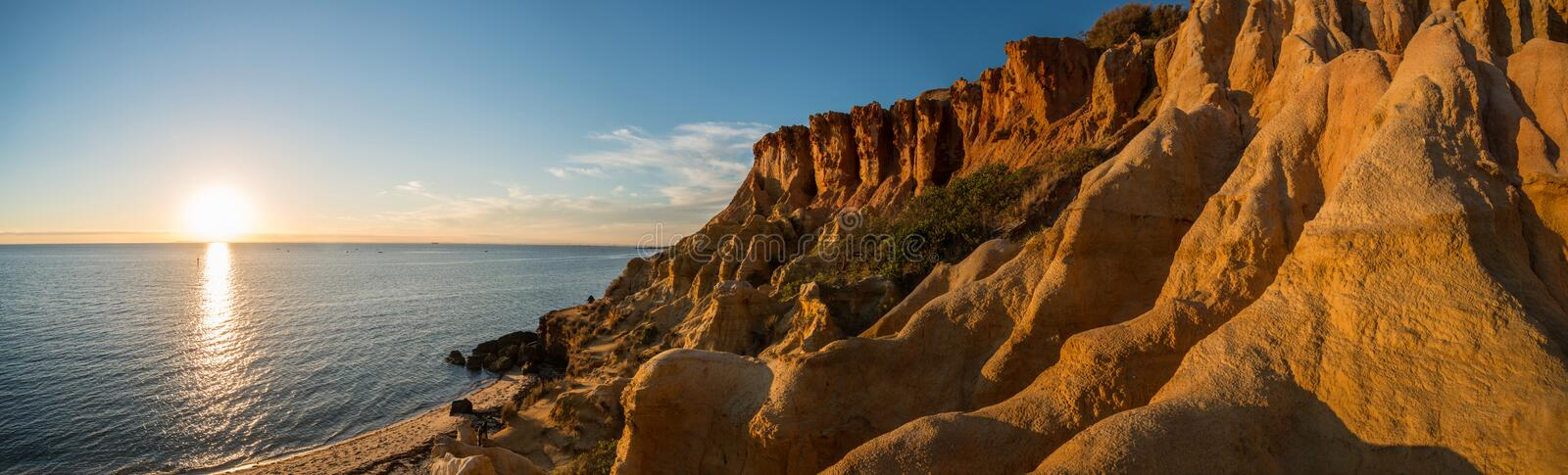 The Black rock beach during the sunset, Melbourne, Australia. Panorama view. Black Rock Beach is a relatively narrow beach lying below 20 m high, vegetated stock image
