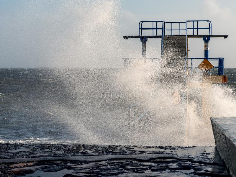 Black Rock diving rock at storm and high tide covered by a giant splash of water. Salthill, Galway city, Ireland. Popular landmark stock photos