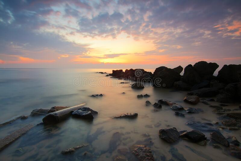 Black Rock Formation on the Sea during Sunset royalty free stock photography