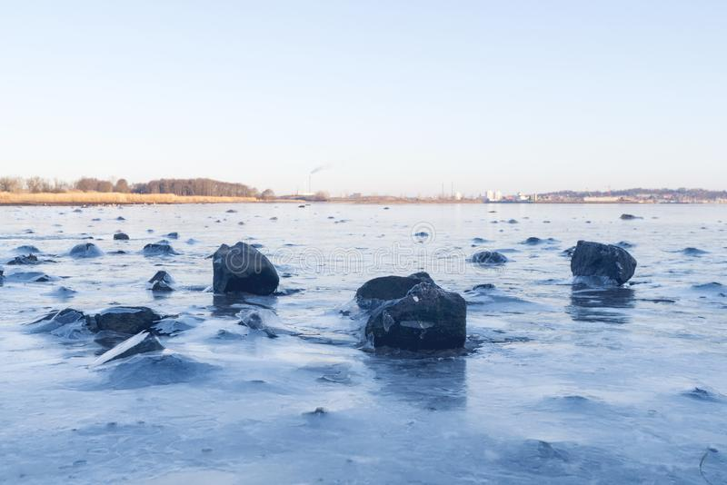 Black rocks in the ice on a frozen lake stock photo