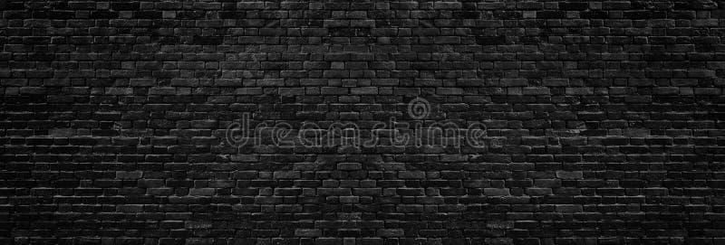 Black brick wall wide texture. Dark brickwork panoramic background stock image