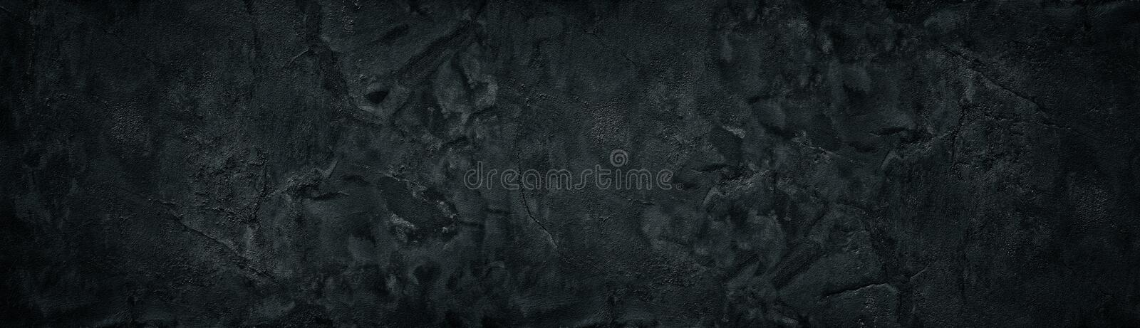Black rough concrete wall wide texture. Fine textured cracked cement plaster surface panorama. Dark panoramic grunge stock photo