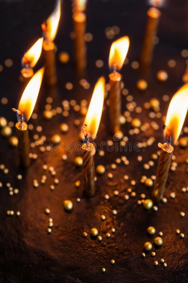 Black round birthday cake with burning golden candles close up. Black round birthday cake with burning golden candles on white background stock photo