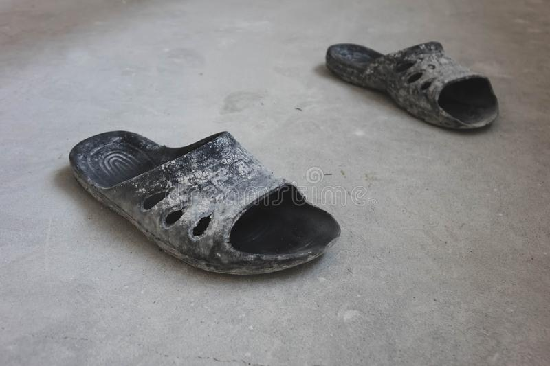 black rubber flip-flops standing on a concrete floor, the concept of repair stock photography