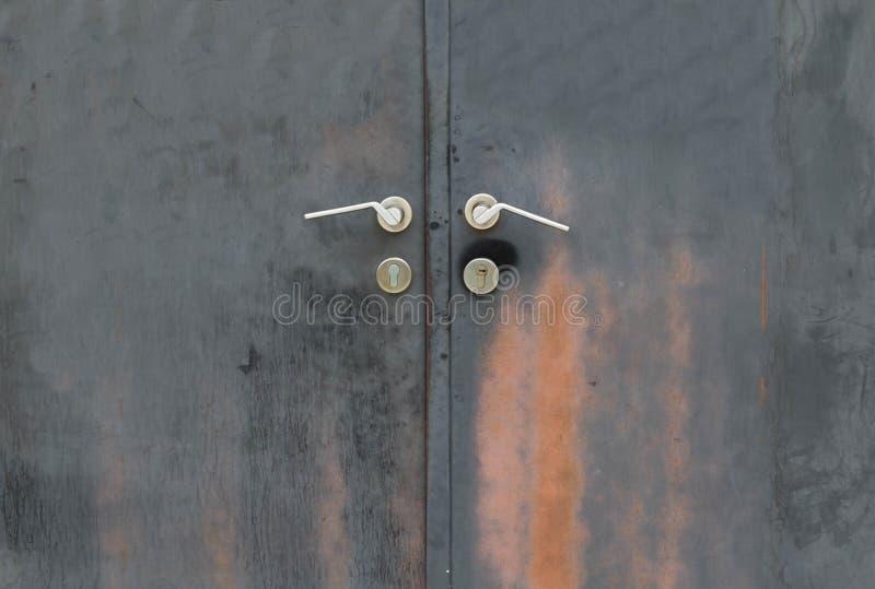 Black rusty iron door with handle stock photography