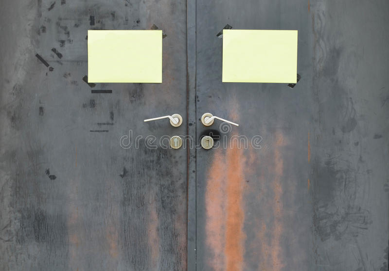 Black rusty iron door with handle and yellow paper attached stock image