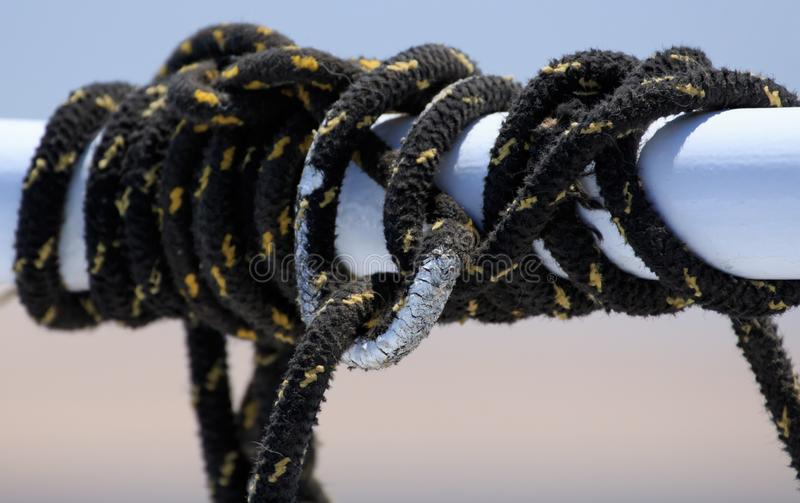 Black sailing ropes crossing in tie knots around boat white tube on blurred deep blue sea water background, picturesque. Abstraction eye catching picture for stock images