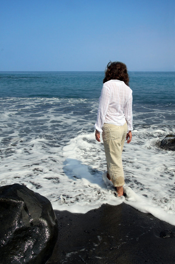 Black sand beach on Big Island. Woman standing on a black sand beach on Big Island, Hawaii royalty free stock image