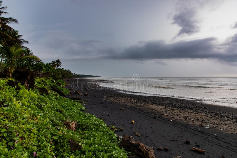 Black sand beach with green vegetation in a stormy day in Bali, Indonesia royalty free stock photo