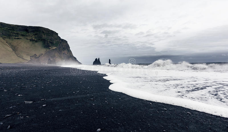 The black sand beach of Reynisfjara in Iceland. The black sand beach of Reynisfjara and the mount Reynisfjall from the Dyrholaey promontory in the southern coast stock photo