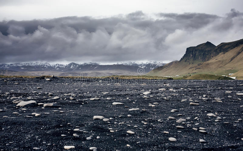 The black sand beach of Reynisfjara in Iceland. The black sand beach of Reynisfjara and the mount Reynisfjall from the Dyrholaey promontory in the southern coast royalty free stock photography