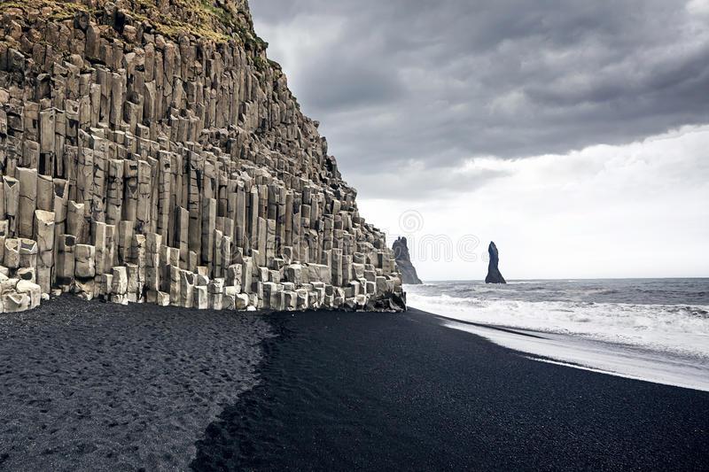 The black sand beach of Reynisfjara in Iceland. The black sand beach of Reynisfjara and the mount Reynisfjall from the Dyrholaey promontory in the southern coast stock image