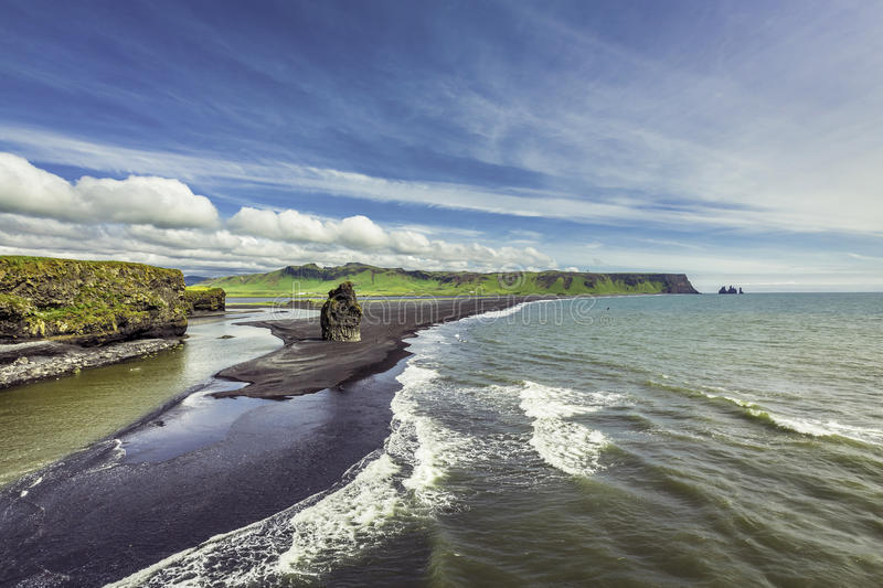The black sand beach with typical Icelandic mountain stock images