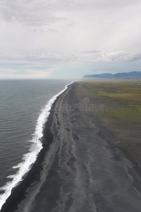 The black sand beach with typical Icelandic mountain landscapes stock image