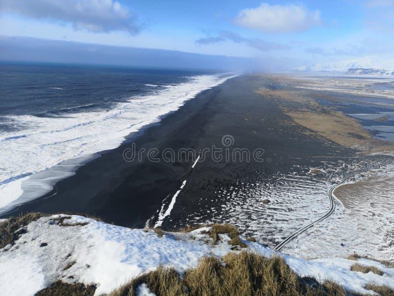 Black Sand coastline landscape in Iceland. Beautiful coastline scene with black sand and snowy mountain under a blue sky stock image