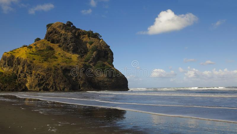 Black Sand Sunny Beach. Mountain Bathed in Sunlight, Covered by Grass and Trees. stock photos