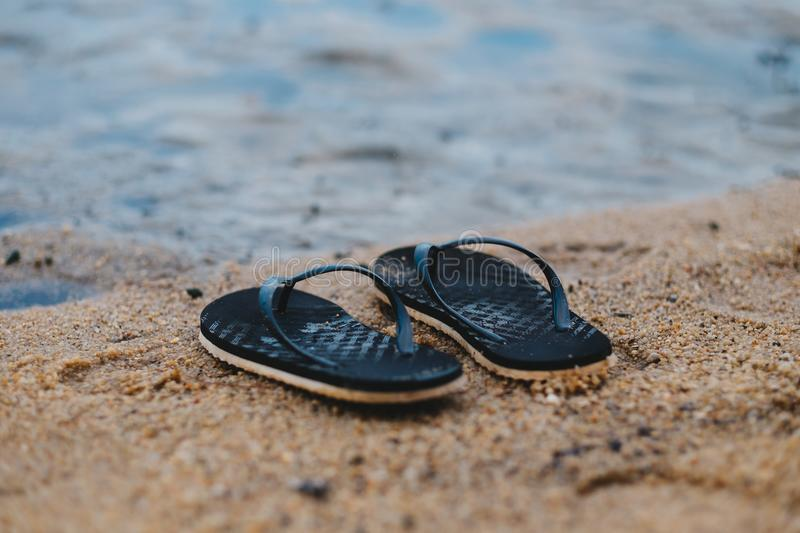 Black sandal putting on sand beach. have pond water are background. this image for nature and equipment concept. Black sandal putting on sand beach. have small stock photos