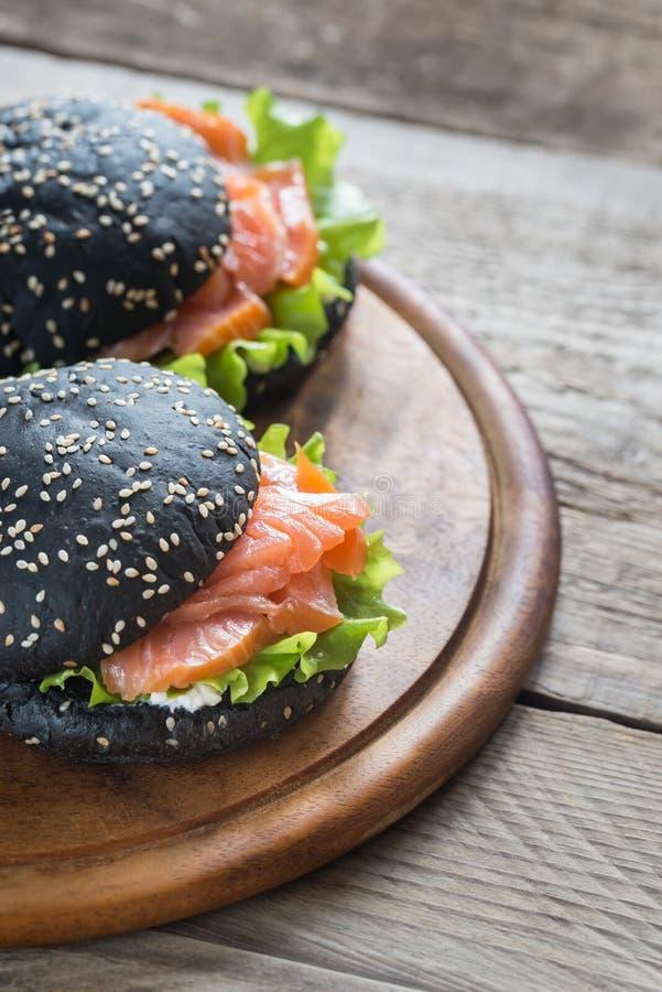 Black sandwich with salmon stock image