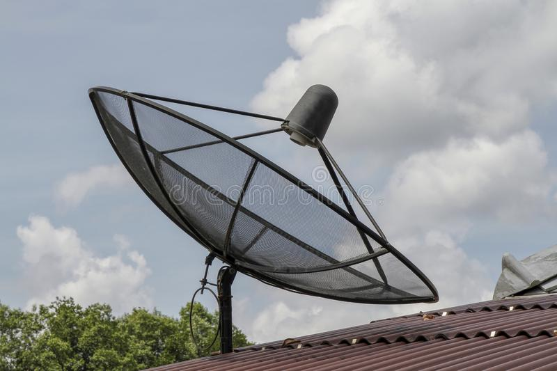 Black Satellite on red roof in thailand. Dish, white, blue, background, modern, sky, old, space, technology, outdoor, home, house, communication, wave royalty free stock photography