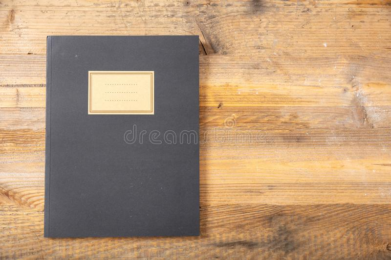 Black school notebook or diary, old fashioned, on wooden background, blank label, space for text, top view. Black school notebook or diary, old fashioned royalty free stock photos